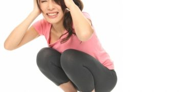 体重計の上で頭を抱える女性