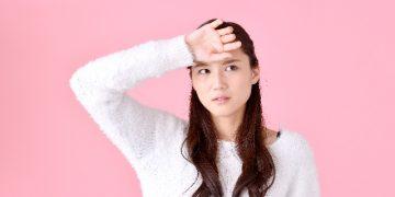 額に手を置いて熱を計る女性