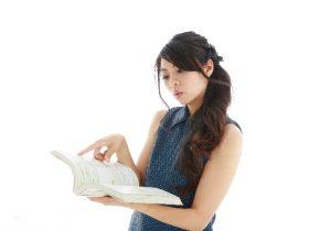 本で調べ物する女性